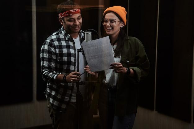 Porträt eines jungen mannes und einer frau im duett, die texte betrachten, die in ein kondensatormikrofon singen, während