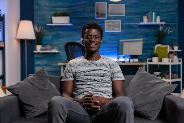 Porträt eines jungen mitarbeiters des afroamerikaners, der auf dem sofa sitzt