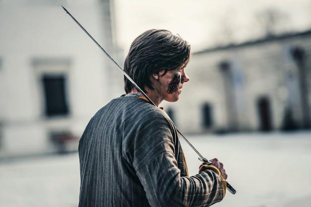 Porträt eines jungen mittelalterlichen kriegers in rüstung mit schwert auf der schulter und wunden im gesicht. im kampf, in der nähe der burg