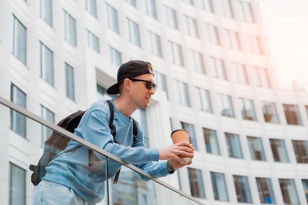 Porträt eines jungen modischen mannes in freizeitkleidung mit kaffee und sonnenbrille und einer mütze