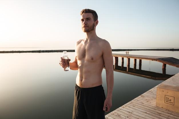 Porträt eines jungen müden sportlers, der wasser nach dem joggen trinkt