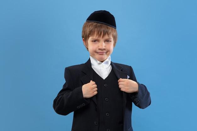 Porträt eines jungen orthodoxen jüdischen jungen lokalisiert auf blauem studio