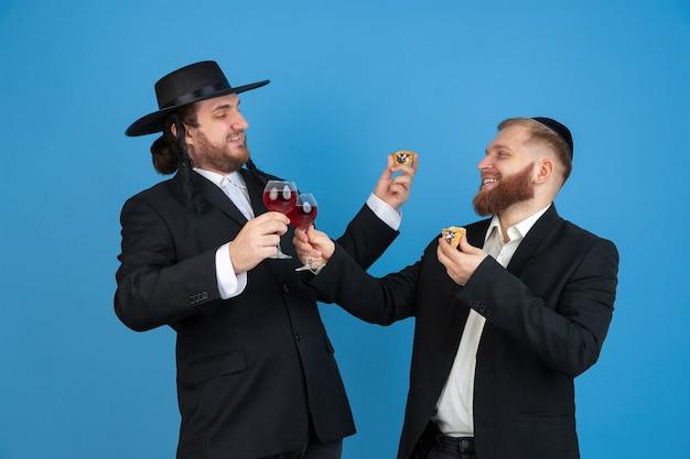 Porträt eines jungen orthodoxen jüdischen mannes lokalisiert auf blauer studiowand, die das passah trifft, das amans ohren mit wein isst