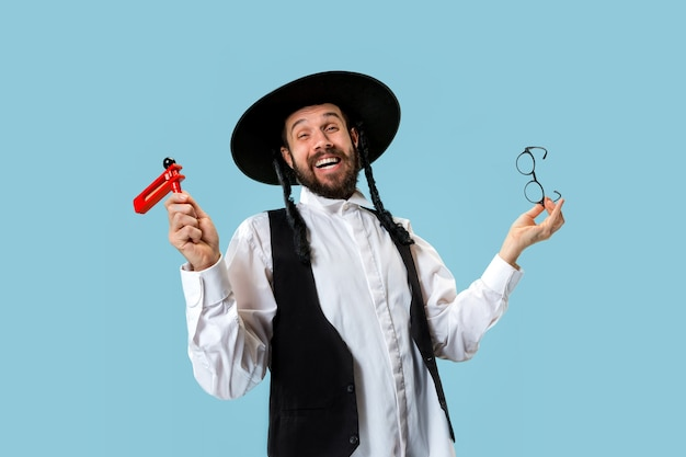 Porträt eines jungen orthodoxen jüdischen mannes mit hölzerner grager ratsche während des festivals purim. feiertag, feier, judentum, tradition, religionskonzept.