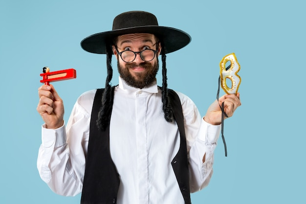Porträt eines jungen orthodoxen jüdischen mannes mit hölzerner grager-ratsche während des festivals purim