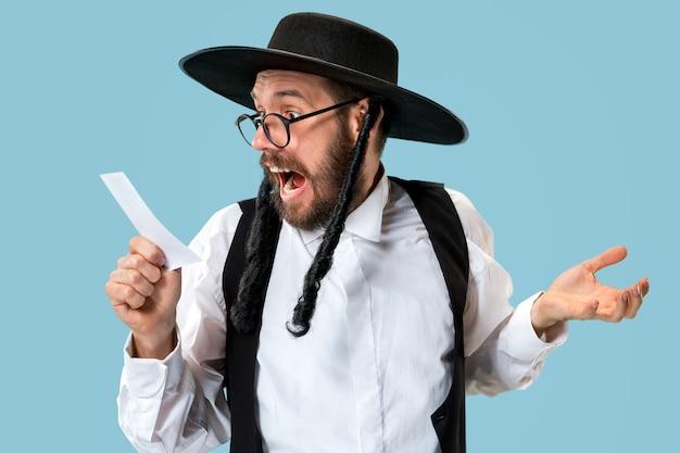 Porträt eines jungen orthodoxen jüdischen mannes mit wettschein im studio.