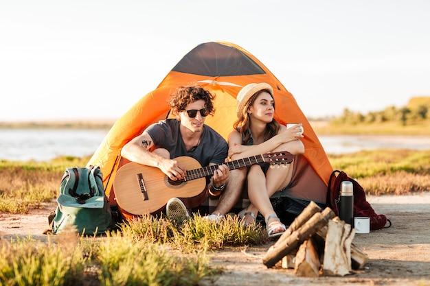 Porträt eines jungen paares, das mit gitarre nahe lagerfeuer beim zelten sitzt