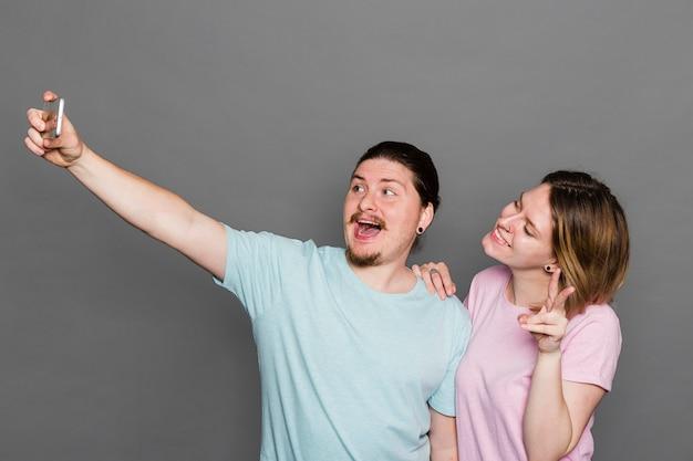 Porträt eines jungen paares, das selfie am intelligenten telefon gegen graue wand nimmt
