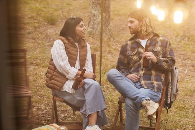 Porträt eines jungen paares, das sich beim camping im freien mit einem von lichterketten beleuchteten van im herbstexemplar entspannt ...