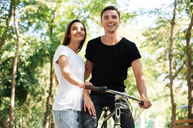 Porträt eines jungen paares, das zusammen auf einem fahrrad fährt