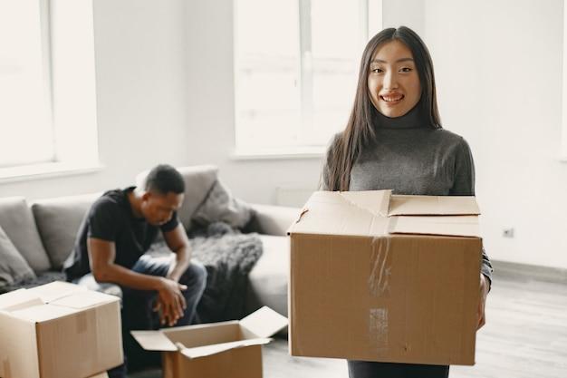 Porträt eines jungen paares mit kartons im neuen zuhause, umzugskonzept.