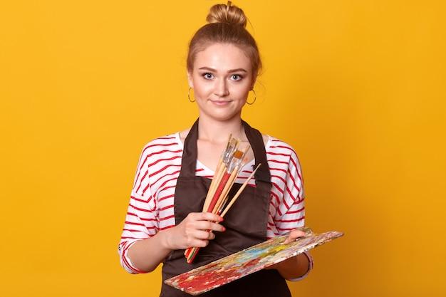Porträt eines jungen positiven kreativen künstlers mit vielen pinseln und einer palette in beiden händen