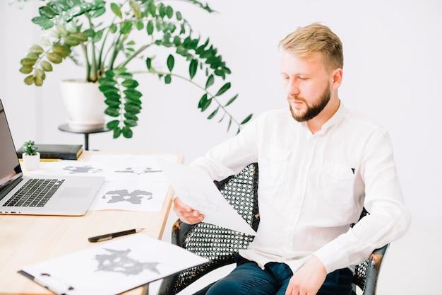 Porträt eines jungen psychologen, der rorschach-inkblot-testpapier im büro betrachtet