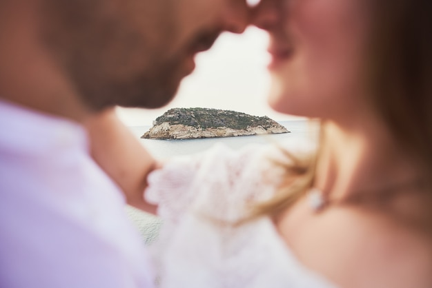 Porträt eines jungen romantischen paares, das auf dem strand küsst und umfasst.