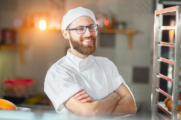 Porträt eines jungen schönen bäckers mit frischem brot