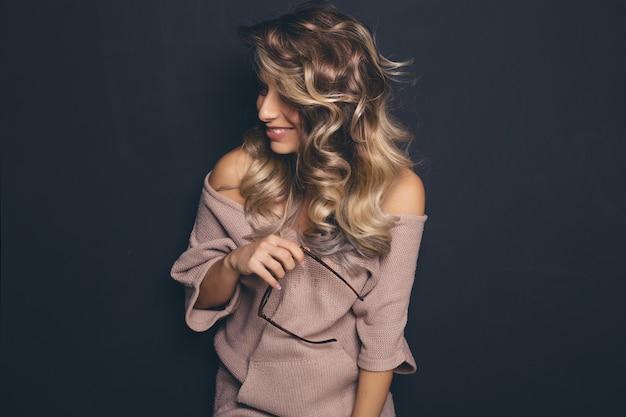 Porträt eines jungen schönen blonden tragenden modischen glases und der zufälligen kleidung und aufstellung über schwarzem hintergrund