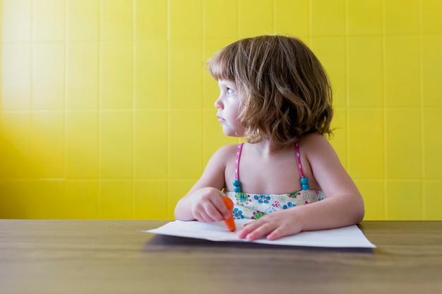 Porträt eines jungen schönen kindermädchens, das zu hause zeichnet. glück und lebensstil drinnen. sommer. gelbe wand