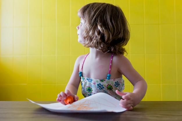 Porträt eines jungen schönen kindermädchens, das zu hause zeichnet. glück und lebensstil drinnen. sommer. gelber hintergrund