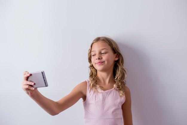 Porträt eines jungen schönen kindes, das einen handy verwendet und ein selfie nimmt. weiße wand. kinder drinnen. lebensstil