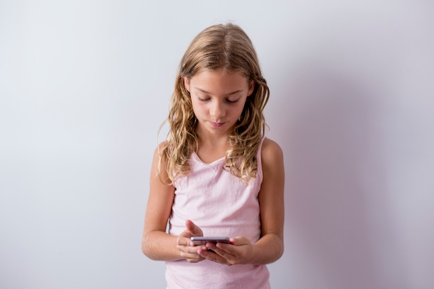 Porträt eines jungen schönen kindes, das einen handy verwendet. weiße wand. kinder drinnen. lebensstil