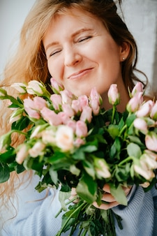 Porträt eines jungen schönen mädchens mit einem rosenstrauß nahe fenster. lockiges fließendes rotes haar.