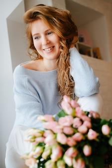 Porträt eines jungen schönen mädchens mit einem strauß rosen nahe fenster. lockig fließendes rotes haar.