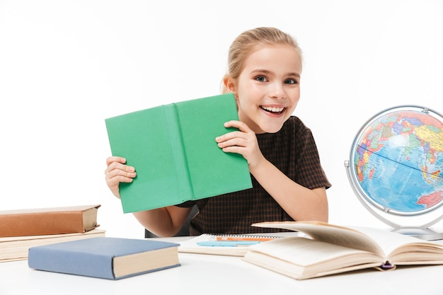 Porträt eines jungen schulmädchens, das bücher liest und hausaufgaben macht, während es am schreibtisch in der klasse sitzt, isoliert über weißer wand