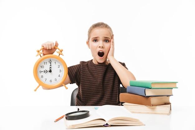 Porträt eines jungen schulmädchens mit großem wecker beim lernen und lesen von büchern in der klasse isoliert über weißer wand