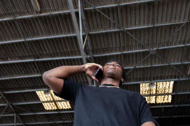 Porträt eines jungen schwarzen jungen, der sein handy benutzt. graffiti-wandhintergrund.