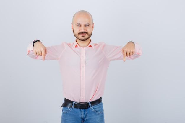 Porträt eines jungen selbstbewussten mannes, der nach unten zeigt