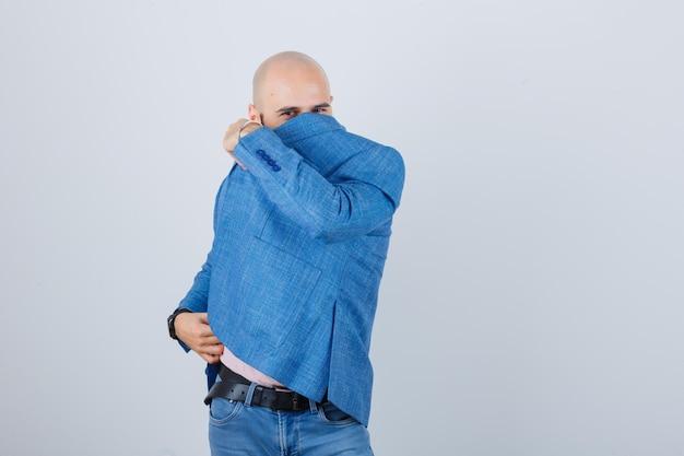 Porträt eines jungen selbstbewussten mannes, der sein gesicht bedeckt