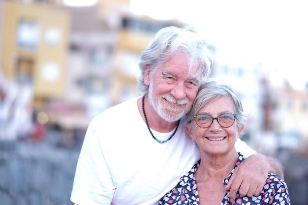 Porträt eines jungen seniorenpaares, das sich im freien bei sonnenuntergang umarmt. kaukasische weißhaarige menschen, die entspannung und freiheit genießen