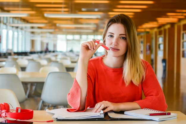 Porträt eines jungen studenten, der an der universitätsbibliothek studiert. bildungs- und lifestyle-konzept.