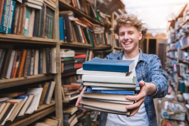 Porträt eines jungen studenten, der ein buch anbietet.