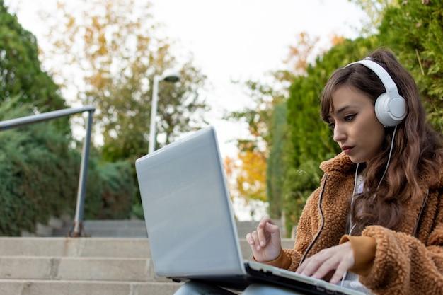 Porträt eines jungen studentenmädchens, das auf der treppe sitzt. mit ihrem laptop arbeiten