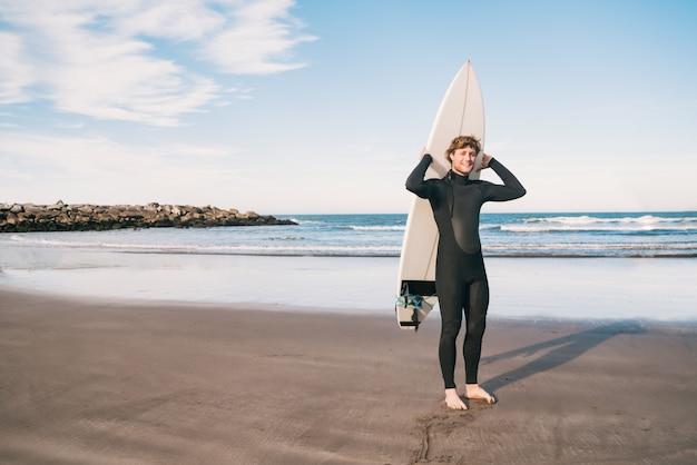Porträt eines jungen surfers am strand, der sein surfbrett hochhält und einen schwarzen surfanzug trägt. sport- und wassersportkonzept.