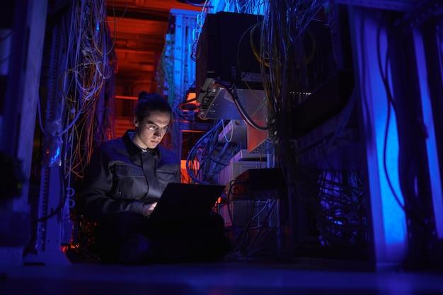 Porträt eines jungen technikers, der ein internet-netzwerk im serverraum einrichtet, platz kopieren