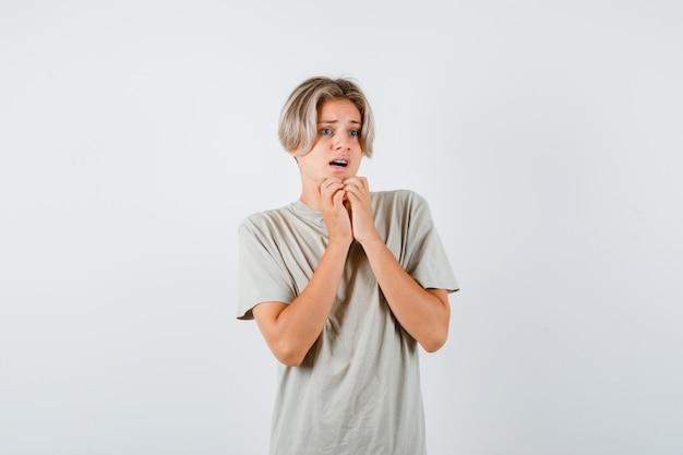 Porträt eines jungen teenagers, der die hände im t-shirt unter dem kinn hält und erschrockene vorderansicht schaut