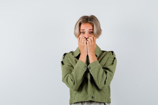 Porträt eines jungen teenagers, der die hände in der grünen jacke auf den mund hält und erschrockene vorderansicht schaut