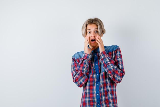 Porträt eines jungen teenagers, der die hände in einem karierten hemd in der nähe des mundes hält und verängstigte vorderansicht schaut