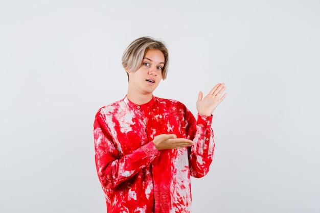 Porträt eines jungen teenagers, der eine einladende geste im hemd zeigt und selbstbewusste vorderansicht sieht