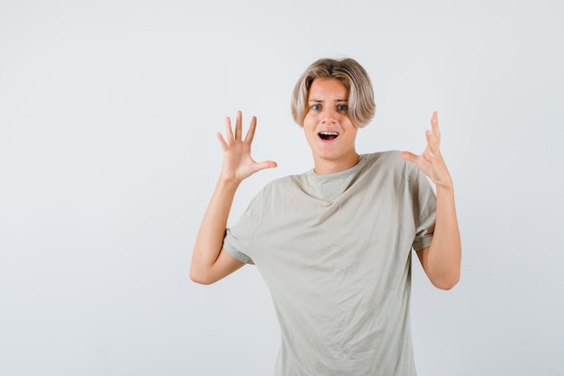 Porträt eines jungen teenagers, der eine kapitulationsgeste im t-shirt zeigt und erschrockene vorderansicht sieht