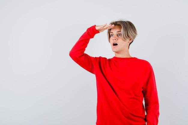 Porträt eines jungen teenagers, der weit weg mit der hand über dem kopf im roten pullover schaut und sich wunderte vorderansicht