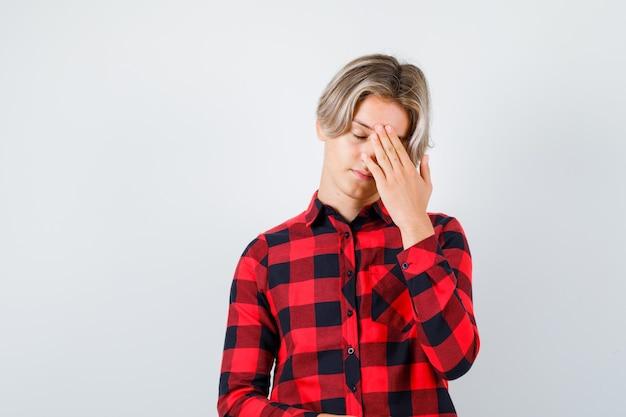 Porträt eines jungen teenagers mit hand auf dem kopf in kariertem hemd und müder vorderansicht