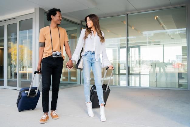 Porträt eines jungen touristenpaares mit koffer beim gehen im freien auf der straße. tourismus-konzept.
