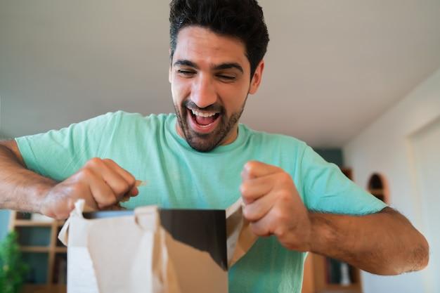 Porträt eines jungen überraschten mannes, der eine geschenkbox öffnet, während er zu hause auf der couch sitzt