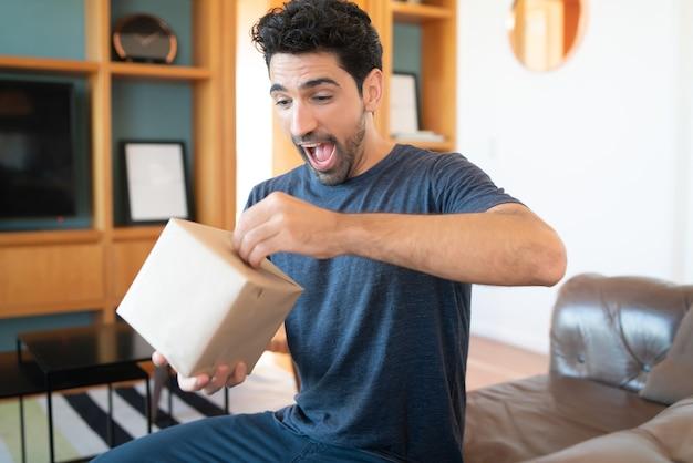 Porträt eines jungen überraschten mannes, der eine geschenkbox öffnet, während er zu hause auf der couch sitzt.