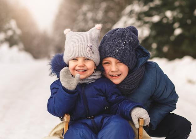 Porträt eines jungen und eines mädchens im wald im winter. bruder und schwester zusammen