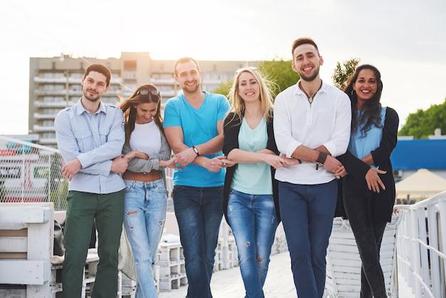 Porträt eines jungen und glücklichen menschen in ruhe auf dem pier. freunde genießen ein spiel auf dem see. positive gefühle.