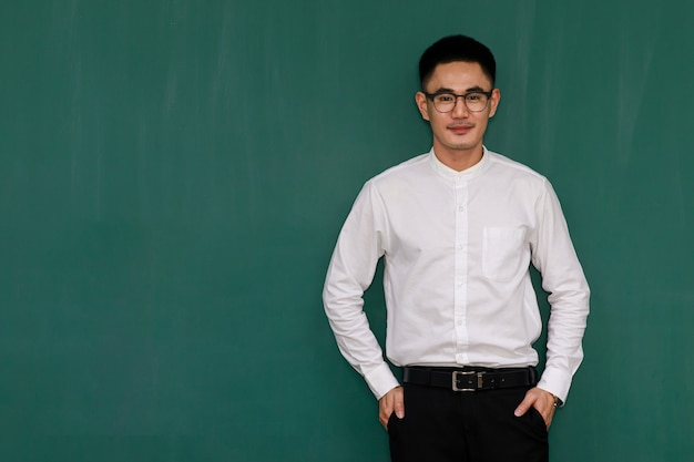 Porträt eines jungen und gutaussehenden asiatischen mannes mit brille und lässiger geschäftskleidung, weißem hemd und schwarzer hose, stehende pose mit selbstbewusstsein mit grünem hintergrund und kopienraum.